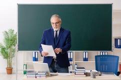 Starzej?cy si? m?ski nauczyciel przed chalkboard zdjęcia stock