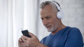 Starzenie się samiec w hełmofonach scrolling ekran smartphone, używać muzycznego zastosowanie obraz stock
