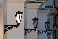 Starzy żelazni uliczni lampiony na białej ścianie Fotografia Stock