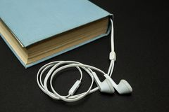 Starzy błękitni książki i białych hełmofony na czarnym tle, zdjęcia royalty free
