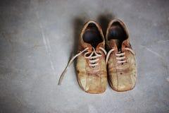 Starzy brown grunge buty na popielatym cementowym tle obrazy stock