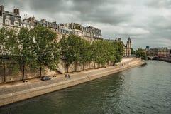 Starzy budynki, deptak i prążkowani drzewa na banku wonton rzeka z światłem słonecznym w Paryż, Zdjęcia Stock