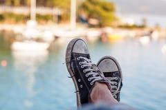 Starzy czarni sneakers na tle morze z jachtami fotografia royalty free