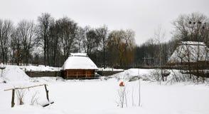 Starzy drewniani domy pod pokrywaj?cym strzech? dachem zakrywaj?cym z ?niegu i woodpile statywowymi pobliskimi starymi drzewami obrazy stock