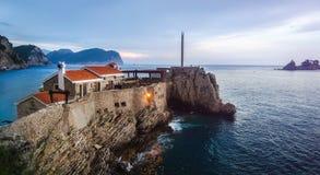 Starzy kamieni domy z czerwień dachami na falezie pochodzi w morze w Petrovac, Montenegro zdjęcia stock