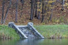 Starzy kroki kamienny spadek na brzeg lasowy staw obraz stock