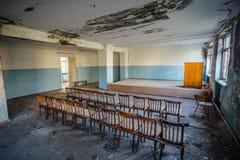Starzy krzesła w zgromadzenie sali zaniechana fabryka fotografia stock