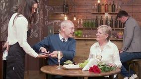 Starzy ludzie w restauracyjnej używa nowej technologii płacić rachunek zbiory