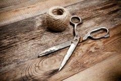 Starzy nożyce i skein jutowi na drewnianym stole Fotografia Stock