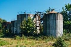 Starzy ośniedziali zaniechani nafciani zbiorniki z schodkami przerastającymi drzewami obraz stock