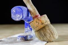 Starzy paintbrushes dla farby, puszki farba na drewnianym stole farba Fotografia Royalty Free