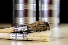 Starzy paintbrushes dla farby, puszki farba na drewnianym stole farba Zdjęcia Royalty Free