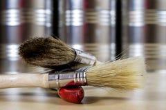 Starzy paintbrushes dla farby, puszki farba na drewnianym stole farba Fotografia Stock