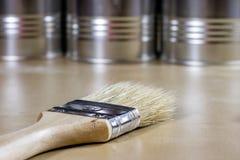 Starzy paintbrushes dla farby, puszki farba na drewnianym stole farba Zdjęcie Royalty Free