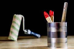 Starzy paintbrushes dla farby, puszki farba na drewnianym stole farba Zdjęcia Stock