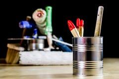 Starzy paintbrushes dla farby, puszki farba na drewnianym stole farba Obraz Stock