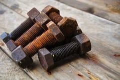 Starzy rygle lub brudzą rygle na drewnianym tle, Maszynowy wyposażenie w przemysł pracie Fotografia Royalty Free