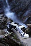 Starzy sneakers na tle skały i siklawa Obrazy Royalty Free