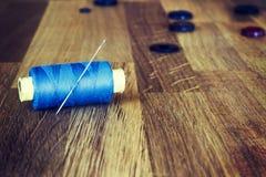 Starzy szy narzędzia na drewnianym tle: cewy, igły, guziki Horyzontalny skład Obrazy Royalty Free