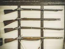 Starzy usługowi karabiny Brytyjski wojskowy z prochowej kolby obwieszeniem na drewnianej ścianie Fowling kawałek na białej ściani fotografia royalty free