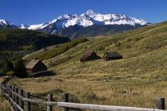 Starzy Utrzymani budynki Pod śnieg Nakrywać górami w południowych zachodach Zdjęcie Stock