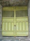 Starzy wapno zieleni metalu kasetonujący drzwi na rolownikach otaczających cegłami obraz stock