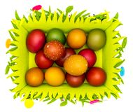 Stash of colorful Easter eggs in a felt Easter basket on white background stock images
