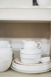 Stack of cooking props. A cabinet full of ceramic props for food photography: plates, bowls, bottles Royalty Free Stock Photo