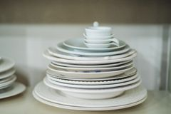 Stack of white plates in a cabinet Stock Photography
