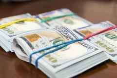 Stashes 100 долларовых банкнот на деревянном столе Стоковая Фотография