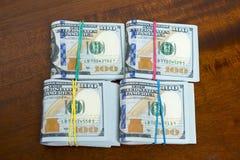 Stashes 100 долларовых банкнот на деревянном столе Стоковое Фото