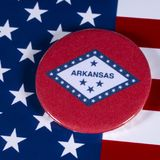 State of Arkansas in the USA. LONDON, UK - APRIL 27TH 2018: The symbol of the State of Arkansas, pictured over the flag of the United States of America, on 27th Stock Photo