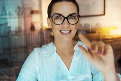 Cheerful woman touching an interactive screen. State-of-the-art technology. Upbeat young woman in eyeglasses raising her finger and touching an interactive Stock Photos