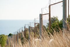 State border razor barbed wire and fence along sea shore and forest. Danger zone royalty free stock image