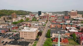 Aerial elevating up over a church clocktower and Charleston West Virginia