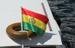 The state flag of Bolivia. The Bolivian flag is flying at the stern of a boat in the town of Copacabana, Bolivia royalty free stock photos