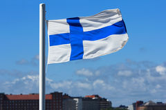 State flag of Finland. State flag of Finland against the blue sky and the silhouette of the city stock photos