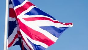 State Flag of the Great Britain. The Big State Flag is illuminated by the sun and flutters epically in the wind against the blue sky. Slow Motion 120 fps stock footage