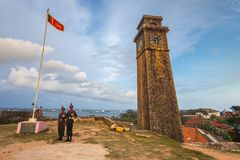 The state flag, two soldiers, clock tower. Galle. The national symbol of the Democratic Socialist Republic of Sri Lanka the state flag and two soldiers Stock Photos