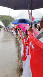 State Flags for LKY's funeral procession. People holding Singapore's national flag while waiting for Mr Lee Kuan Yew's hearse to pass by to bid their final Stock Image