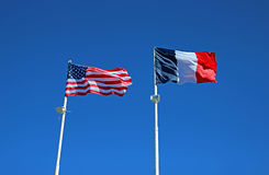 State flags of the United States of America and France. Against the blue sky Stock Photos