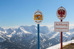 State German-Austrian border sgnboards on top Alpine mountain ridge Royalty Free Stock Photos