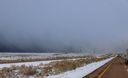 State road 64 to New Mexico, in winter. With clear roads bordered by snow covered royalty free stock image