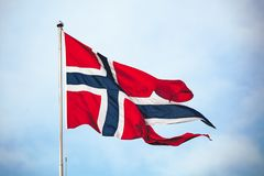 State and war flag of Norway. Waving over cloudy sky background stock image
