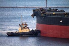 Statek berthing przy portem z holownik pomocą Zdjęcia Stock
