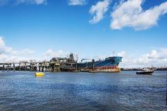 Statek przy doku rozładunkiem przy Wirral składowymi zbiornikami obrazy stock