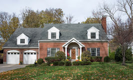 Stately Cape Cod House in Fall. Larger Cape Cod house in fall with mums & pumpkins Stock Photo