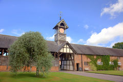 Stately home in Cheshire, England. Barn with clock tower at the entrance  of a historic Arley Hall in Cheshire, England Royalty Free Stock Image