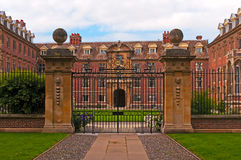 Stately home and gate. Exterior of historic stately home with closed metal gate in foreground royalty free stock images