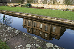 Stately home reflection. Reflection in garden ornamental pond of victorian stately home royalty free stock photos